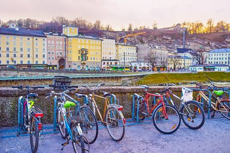 SALZBURG, AUSTRIA - FEBRUARY 27, 2019: The small bicycle parking on the embankment with a view of Altstadt district on the other bank of  Salzach river, on February 27 in Salzburg