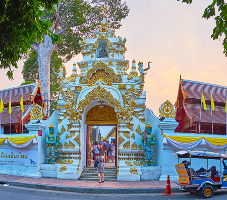 CHIANG MAI, THAILAND - MAY 2, 2019: The entrance gate of Wat Chedi Luang with rich gilt molding, carved patterns, Wheels of Dharma and scultpures of devatas, on May 2 in Chiang Mai