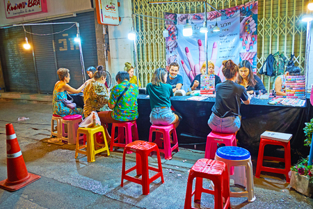 CHIANG MAI, THAILAND - MAY 2, 2019: The street nail salon offers manicure service till late night, neighboring with Warorot Night Market, on May 2 in Chiang Mai Editorial