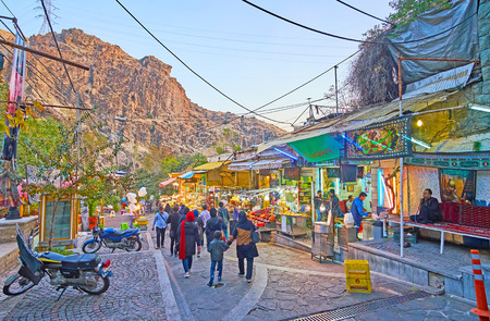 TEHRAN, IRAN - OCTOBER 25, 2017: The evening walk through the  market street of Darband with a view on small stalls, shops and rocks, lighted with sunset rays, on October 25 in Tehran Editorial