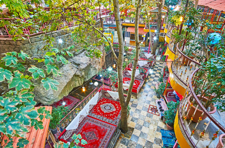The valley of Darband river, stretching along the rocky gorge, is occupied with many restaurants, cafes and outdoor lounge zones with trestle-beds and tables under the shady trees, Tehran, Iran