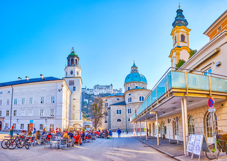 SALZBURG, AUSTRIA - FEBRUARY 27, 2019: The scenic outdoor cafe in Mozartplatz among famous landmarks of old town is a fine place to have a short brake, on February 27 in Salzburg Editorial