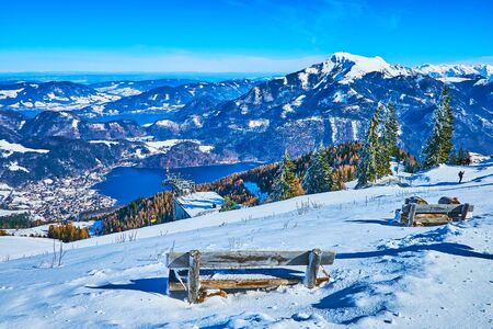 The old wooden benches are hidden in deep snowdrifts on the slope of Zwolferhorn mount, overlooking Salzkammergut scenery, Wolfgangsee and Mondsee lakes, St Gilden, Austria