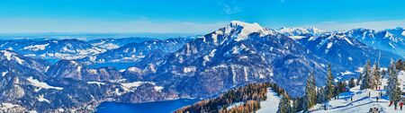Alpine panorama from the top of Zwolferhorn mount with sharp peaks, rocky slopes, winter forests, blue Wolfgangsee and Mondsee lakes, St Gilden, Salzkammergut, Austria