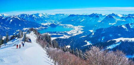 The peak of Zwolferhorn mount attracts tourists and sportsmen to enjoy great panorama of snowy rocky Alps and blue Wolfgangsee lake, St Gilden, Salzkammergut, Austria