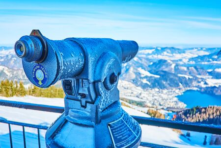 The viewpoint of Zwolferhorn mount is equipped with coin-operated telescope (tower viewer), showing Wolfgangsee valley, lake, St Gilden town, mountains of Salzkammergut, Austria