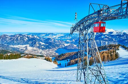 The view from the top of Zwolferhorn mountain on the cable car tower, colorful vintage cabins and the Wolfgangsee lake valley, surrounded by Alps, St Gilden, Salzkammergut, Austria
