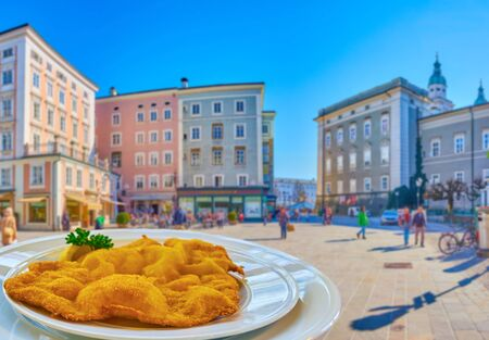 Tasty Austrian Shnitzel in outdoor cafe in Alter Markt square  with a view on medieval edifices of Salzburg Stockfoto
