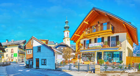 ST GILGEN, AUSTRIA - FEBRUARY 23, 2019: The panoramic streetscape with wooden cottages and parish church's belfry on background, on February 23 in St Gilgen Editorial
