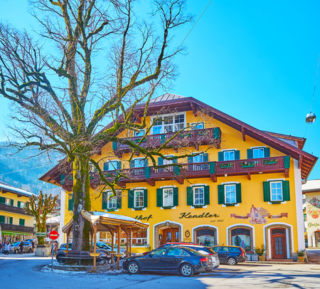 ST GILGEN, AUSTRIA - FEBRUARY 23, 2019: The facade of old guest house, located in villlage center and decorated with carved wood and painted details, on February 23 in St Gilgen Redakční