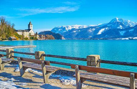 Ciesz się spacerem wzdłuż nabrzeża jeziora Wolfgangsee z ławkami, zabytkowymi latarniami i fantastycznymi widokami na ośnieżone Alpy i kościół pielgrzymkowy za jeziorem, St Folfgang, Salzkammergut, Austria Zdjęcie Seryjne