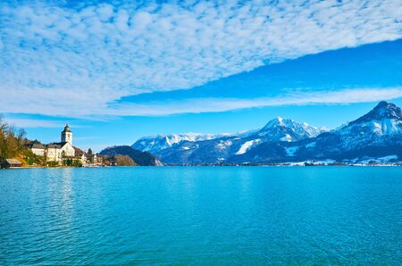 The scenic cloudscape over the Wolfgangsee lake and snowy Salzkammergut mountain range of  Northern Limestone Alps, the tall belfry of Pilgrimage Church is seen on the distance, St Wolfgang, Austria