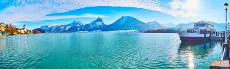 Panorama of Wolfgangsee lake with Pilgrimage Church, Strobl town on opposite bank, snowy Alps of Postalm region and ferries in terminal, St Wolfgang, Salzkammergut, Austria 写真素材 - 130150284