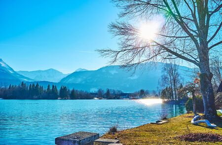 The lakeside walk with a view on shiny rippled surface of azure Wolfgangsee lake, that reflects the sun rays, St Wolfgang, Salzkammergut, Austria 写真素材 - 130150288