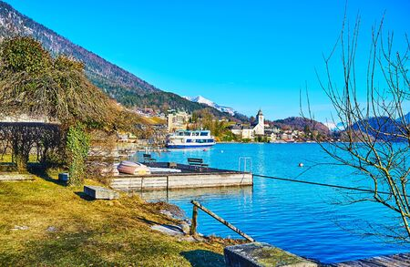 Walk by the Wolfgangsee, enjoy the lakeside park, watch the bright blue rippled surface of the lake, ferries in port and the Pilgrimage church on background, St Wolfgang, Salzkammergut, Austria