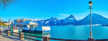 Panorama of St Wolfgang ferry port on Wolfgangsee lake with rocky Alps of Postalm region on background, Salzkammergut, Austria