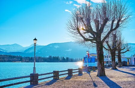 The sunny winter embankment of Wolfgangsee lake with a view on park and vintage streetlights, St Wolfgang, Salzkammergut, Austria