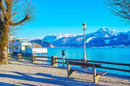 Relax on the old bench in quiet park on the bank of winter Wolfgangsee lake with a view on Alps of Postalm region, St Wolfgang, Salzkammergut, Austria 写真素材 - 130150244