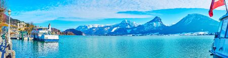 The tourist ferries, moored at the bank of Wolfgangsee lake, surrounded by snowy Alpine range, St Wolfgang, Salzkammergut, Austria 写真素材