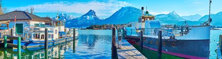 Panorama of the shipyards on Wolfgangsee lake with docked vintage ferries and Alps of Postalm region on background, St Wolfgang, Salzkammergut, Austria 写真素材 - 130150253