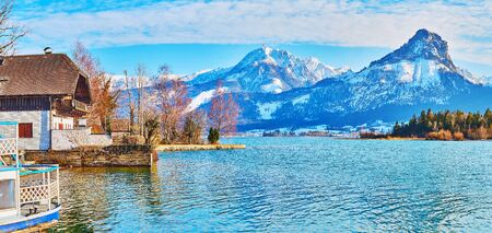 The scenic lakeside view from the bank of Wolfgangsee on winter trees and massive rocky Labenberg and Pitschenberg mountains of Postalm region, St Wolfgang, Salzkammergut, Austria 写真素材 - 130150254