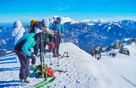 ST GILGEN, AUSTRIA - FEBRUARY 23, 2019: The group of skiers prepares to downhill from the Zwolferhorn mountain peak, on February 23 in St Gilgen