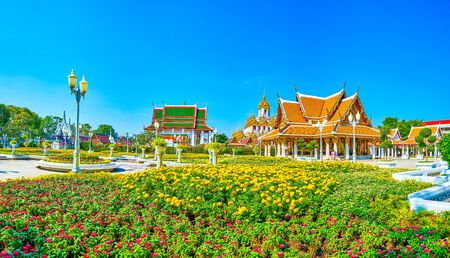 The beautiful flower beds in small Royal Pavilion Mahajetsadabadin park with Wat Ratchanatdaram on the background, Bangkok, Thailand Reklamní fotografie