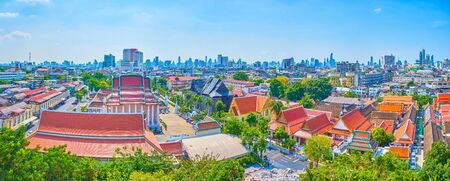 Panoramic view on old buddhist religion complex of Wat Saket Temple with large Wednesday Buddha Temple and numerous small shrines and building of various purposes, Bangkok, Thailand