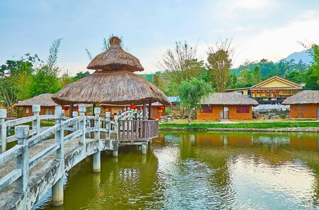 The banks of the small pond are connected with scenic bridge with covered pavilion in the middle, mountain Chinese tea village of Santichon, Thailand 写真素材 - 130154746