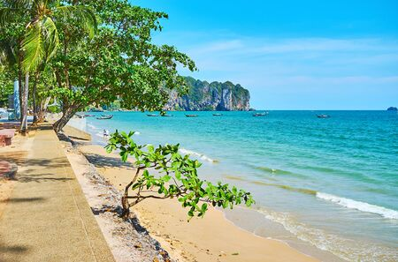 Walk the shady seaside promenade of Ao Nang and watch the golden beach, turquoise waters of Andaman sea, lush tropical greenery and rocky cliffs on background, Krabi, Thailand
