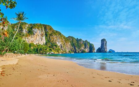 Panorama of the Ao Nang coast from the Monkey beach, lined with jungle and huge limestone rock formations, Krabi, Thailand