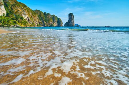 Enjoy the gentle tide waves on Monkey beach with a view on Ao Nang scenic coast with tall rocky cliffs, islets, giant boulders and tropical forests, Krabi, Thailand Imagens