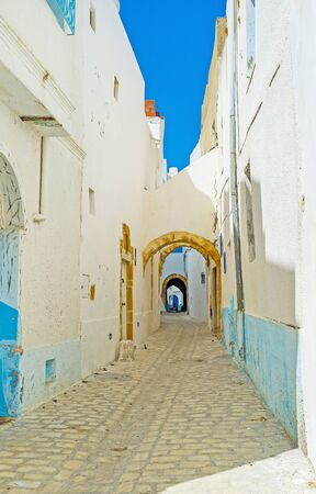 The narrow street of Arab Medina is lined with shabby living houses, facing the street with white blank walls, Bizerte, Tunisia