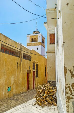 Rectangular minaret of old Kasbah mosque rises over the houses of Bizerte Medina, with pile of firewood in the street on the foreground, Tunisia