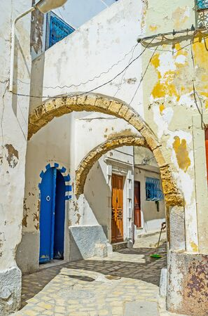 Walk through the old arched passes in shabby street of Arab Medina with crumbling paint and plaster on walls, Bizerte, Tunisia