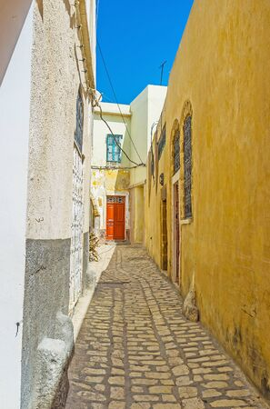 The narrow dead end street of Arab Medina with tall blank house walls and colored wooden doors, Bizerte, Tunisia