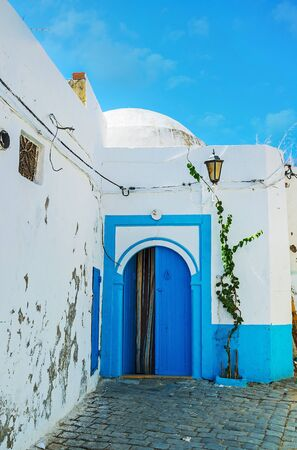 Traditional white house in medieval Arab Medina with bright blue door frame and arched wooden door, Bizerte, Tunisia