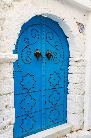 The ornate Arab style wooden door of bright blue color with Islamic pattern of rivets, vintage knob knockers and traditional horseshoe frame, Medina of Bizerte, Tunisia