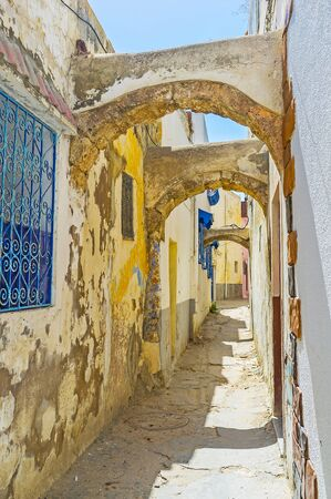 Walk the narrow shabby alley of Arab Medina with crumbling plaster and paint, preserved arched passes and blue window grills, Bizerte, Tunisia