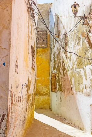The narrow backstreet with leaning house, coated in faded paint and crumbling plaster, Medina of Bizerte, Tunisia