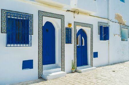 Traditional white house is decorated with bright blue window grills, shutters and doors, those have patterns of rivets, vintage knobs and tile frames with fine Islamic patterns, Bizerte, Tunisia