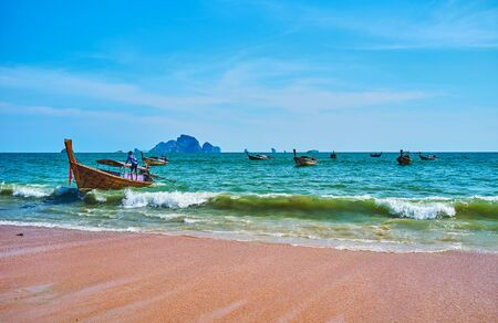 Enjoy the tide on the Ao Nang beach with a view on foaming waves, wooden longtail boats and rocky islands on the background, Krabi, Thailand