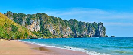 Panorama of the comfortable sand beach, lined with lush tropical greenery and massive rock formation, seen on the background, Ao Nang, Krabi, Thailand Reklamní fotografie