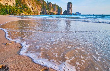 The rocky Ao Nang coast is reflected in foaming tidal waves on Monkey beach, Krabi, Thailand