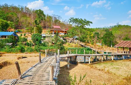 Walk the curved narrow  Boon Ko Ku So bamboo bridge - the interesting landmark, located amid the agricultural lands and dried paddy fields, Pai, Thailand Zdjęcie Seryjne - 130155114