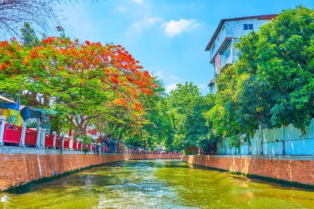 The tourist ferry floats along the narrow  Bang Lamphu Khlong (canal), lined with shabby houses and lush gardens of old town, Bangkok, Thailand 写真素材 - 130155174