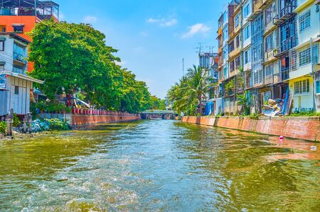 Enjoy the fast trip through the narrow Bang Lamphu Khlong (canal), lined with shabby living quarters, slums and narrow streets of Bangkok, Thailand 写真素材 - 130155187