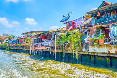 The poor residential houses built on the bank of Saensaep khlong is seen from the ferry sailing along the canal, Bangkok, Thailand 写真素材 - 130155188