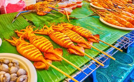 The grilled squids and other seafood on the showcase of the food market in Central World Plaza in the heart of business district in Bangkok, Thailand Stock fotó