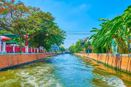The trip along narrow khlongs (canals) in old town passing famous tourist destinations on fast tourist ferry, Bangkok, Thailand 写真素材 - 130155208
